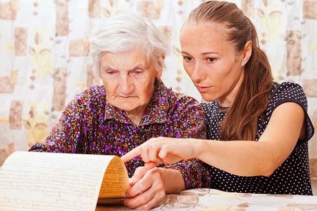 Девушка помогает пожилой женщине читать