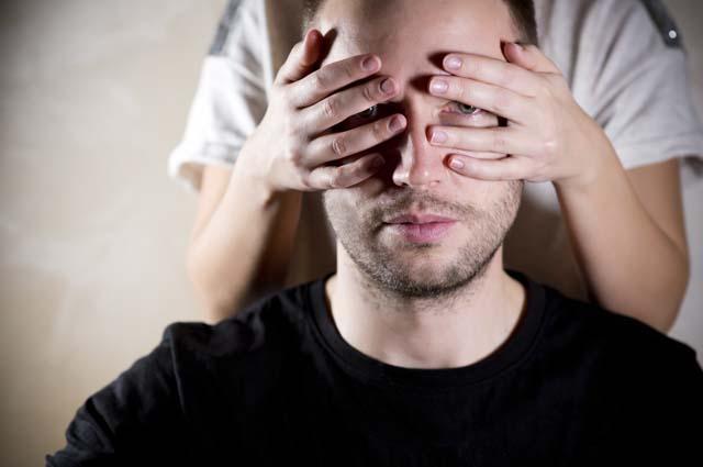 Женщина закрывает мужчине глаза руками
