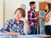 Женщина сидит за столом, муж с женой конфликтуют