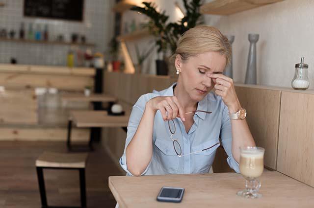 Женщина устала, сидит за столом на кухне