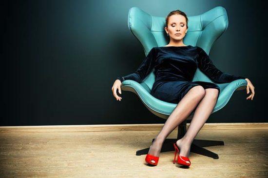 Красивая девушка сидит в кресле закрыв глаза