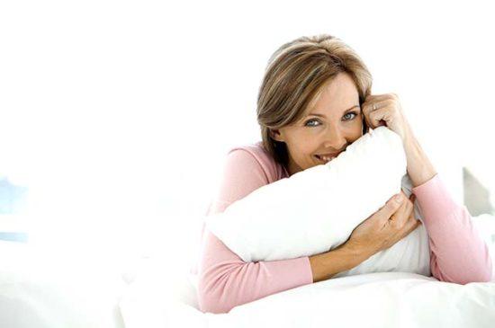 Красивая женщина средних лет закрывается подушкой
