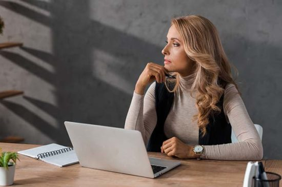Блондинка размышляет за компьютером