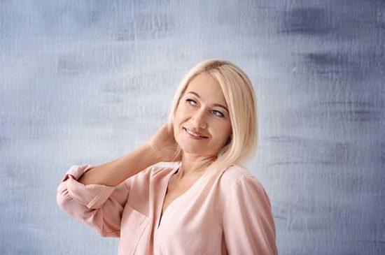 Красивая взрослая женщина поправляет волосы