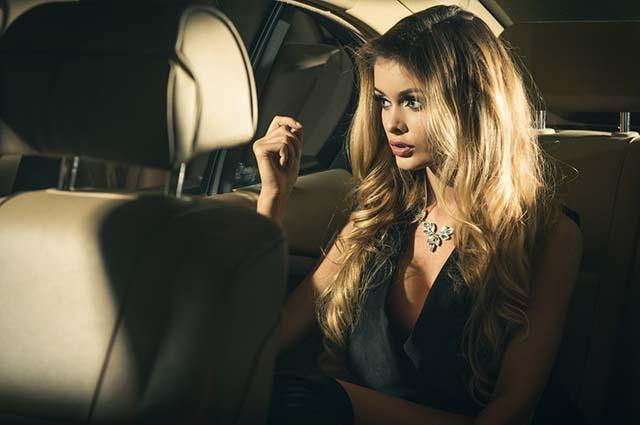 Красивая девушка на заднем сиденье автомобиля