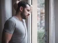 Мужчина в депрессии дома у окна
