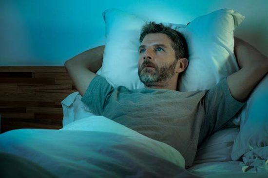 Мужчина лежит в кровати и размышляет