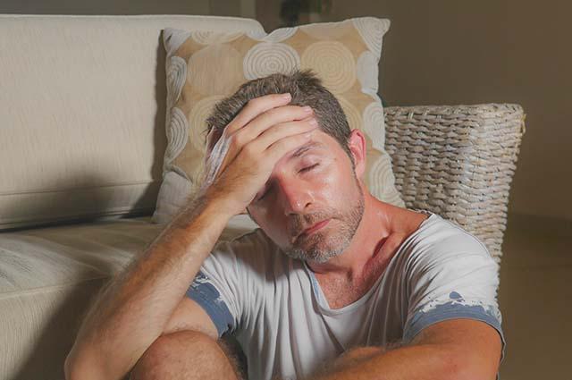 Мужчина сидит у дивана, расстроен