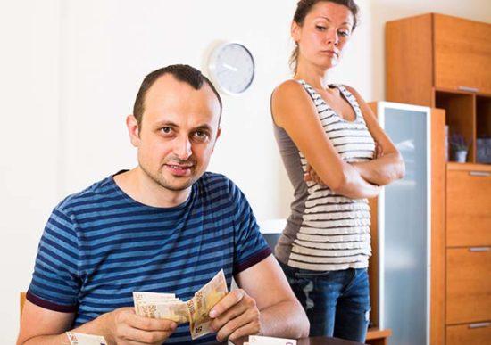 Мужчина считает деньги, женщина смотрит