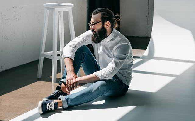 Мужчина в очках сидит на полу