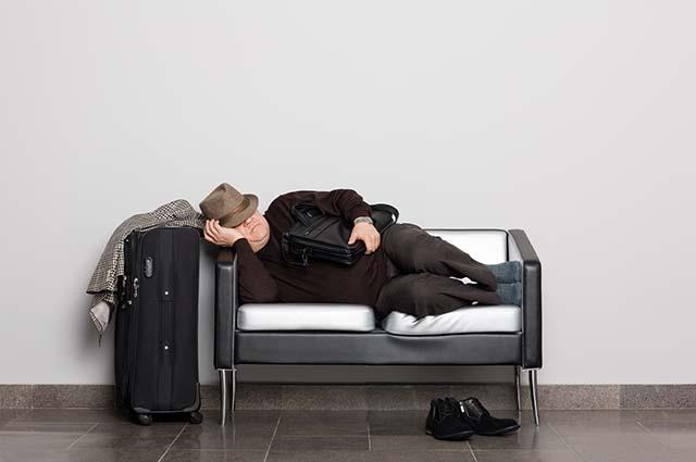Мужчина спит на диване, рядом стоит чемодан