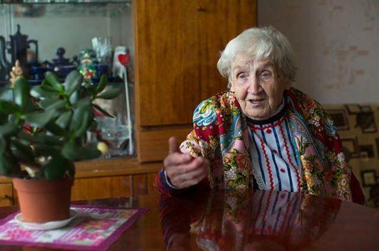 Пожилая женщина сидит за столом жестикулирует
