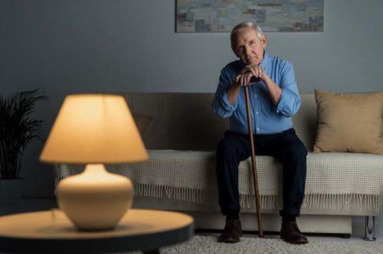 Пожилой человек сидит на диване
