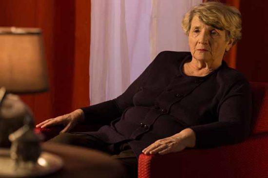 Расстроеная пожилая женщина сидит в кресле