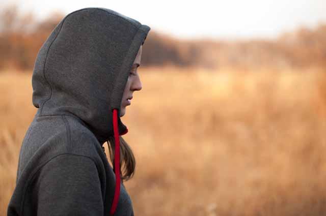 Девушка в спортивной толстовке в поле