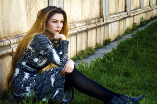 Девушка грустит, сидя на траве