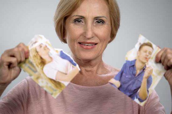 Женщина рвет фотографию