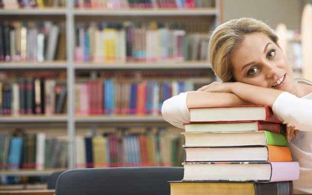 Девушка библиотекарь сидит с книгами