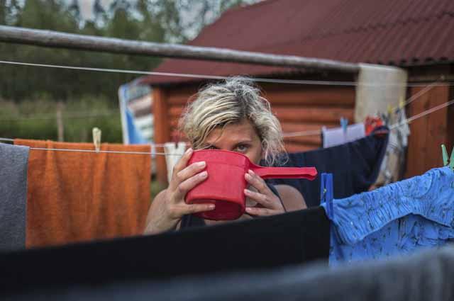 Девушка пьет воду из ковша