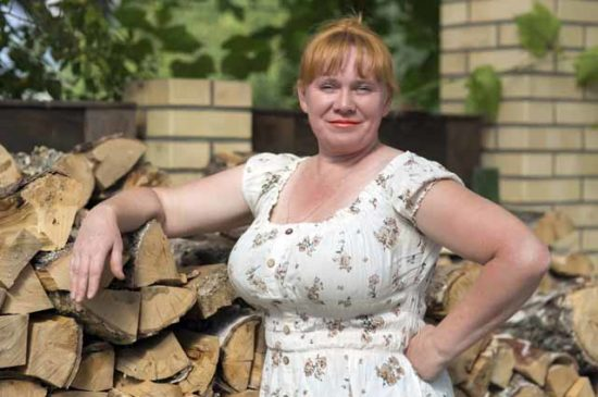 Женщина позирует на фоне дров