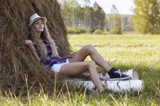 Красивая девушка у копны в поле