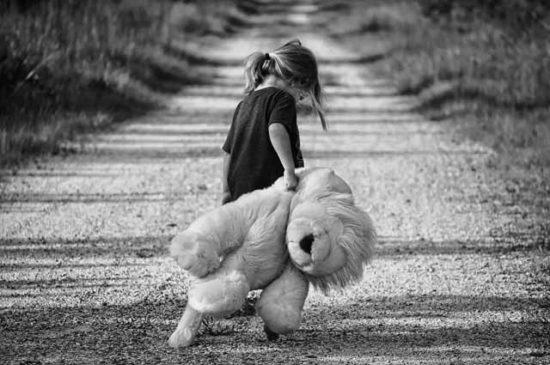 Ребенок с плюшевым мишкой на грунтовой дороге